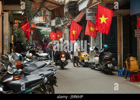Motorcycles in and Vietnamese flags in busy Old Quarter, Hanoi, Vietnam - Stock Photo