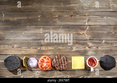 Ingredients for cooking black burger. Grilled meat patty, buns, onion, tomatoes, lettuce, pickles, sauce, cheese - Stock Photo