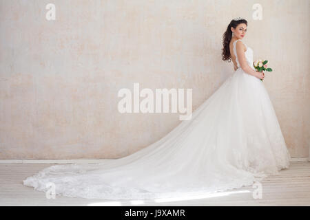 Princess Bride in a wedding dress standing in a room of vintage - Stock Photo