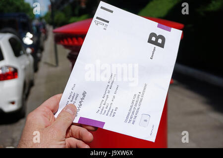 UK, London : A postal voting envelope is posted into a royal mail letter box in London ahead of the 2017 general - Stock Photo