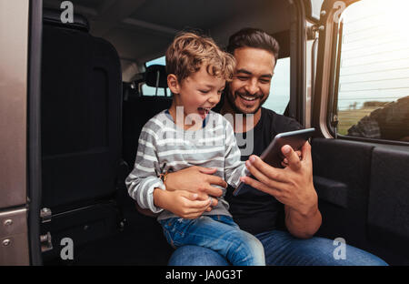 Shot of happy father and son sitting at the back of the car and looking at digital tablet. Young man and little - Stock Photo
