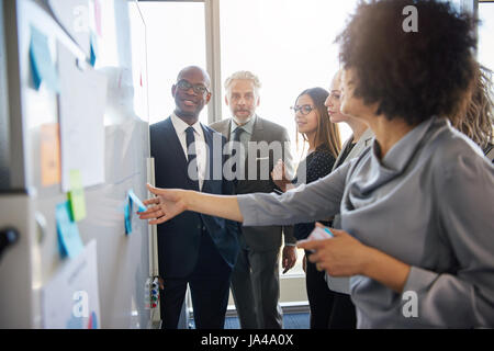 Group of mixed business people having a meeting using a white board in bright office space - Stock Photo