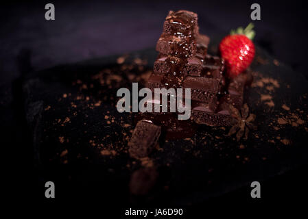One red straberry on a dark  chocolate - Stock Photo