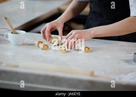 Horizontal indoors crop shot of hands of woman working with knead and forming pasta in kitchen. - Stock Photo
