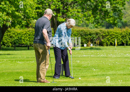 Senior couple playing mini golf (putting) in Summer in the UK. - Stock Photo