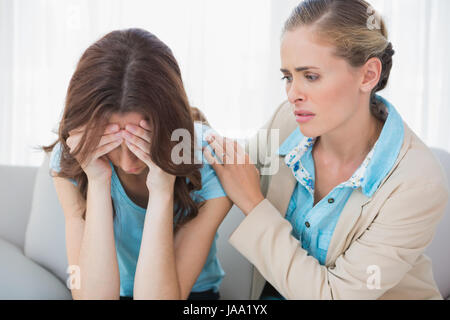 Crying woman with her concerned therapist sitting on the sofa - Stock Photo