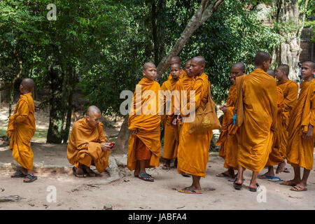 Young Buddhist monks at the entrance to Ta Prohm, Angkor, Siem Reap, Cambodia - Stock Photo