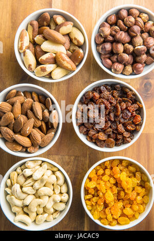 Various nuts and raisins in bowl on wooden table. - Stock Photo