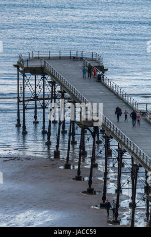 High view of people on Victorian pleasure pier, jutting out into North Sea on grey spring day - Saltburn-by-the - Stock Photo