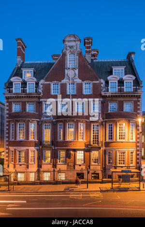 Evening view of The Grand Hotel & Spa, (5-star luxury hotel) with a golden glow from street lights & behind windows - Stock Photo