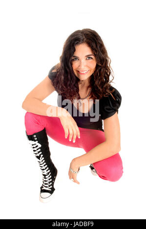 A slim young woman in a black top, pink jeans and black boots crouching for white background, looking up. - Stock Photo