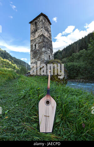 Georgian national musical instrument of Panduri with a medieval tower in the background, in the Svaneti region of - Stock Photo