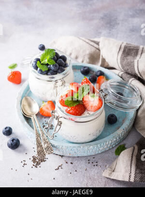 Chia Pudding for breakfast in glass jars garnished with berry in two portions on light gray stone background with - Stock Photo
