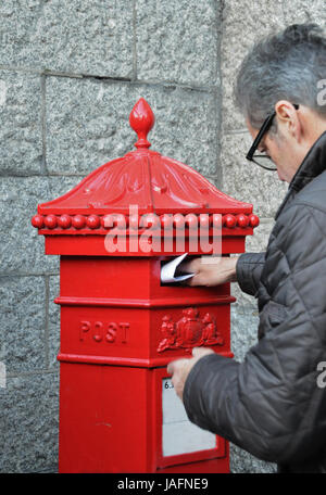 Man posting a letter in a Victorian post box - Stock Photo