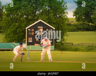 Game of Cricket being played in typical British village. - Stock Photo