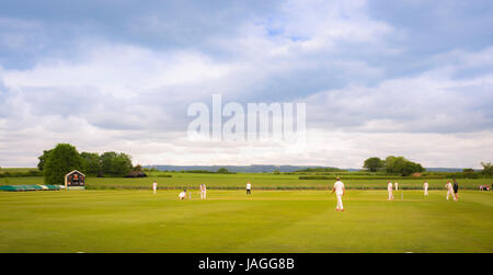 Game of Cricket being played in typical British village of Sessay with the White Horse in the background. - Stock Photo