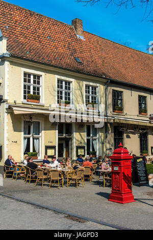 Tourists seated at tables in an outdoor cafe, Bruges, West Flanders, Belgium - Stock Photo
