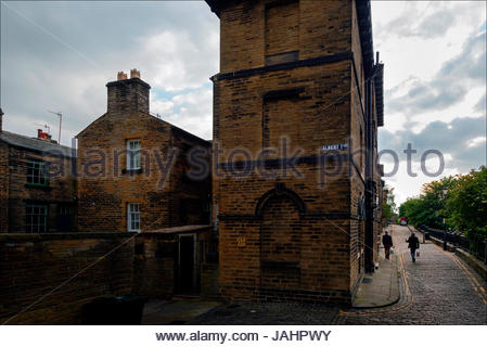 Residents stroll home from the pub in Saltaire, a Victorian model village in Bradford West Yorkshire, along the - Stock Photo