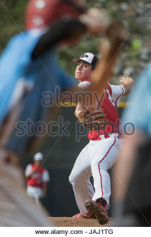 A sixteen-year-old boy pitching in a travel baseball game. - Stock Photo