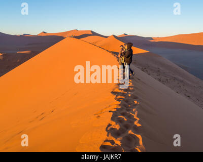 SOUSSUSVLEI, NAMIBIA - JUNE 20, 2016: People watching sunrise form the Dune 45 in the Sossusvlei area of the Namib - Stock Photo