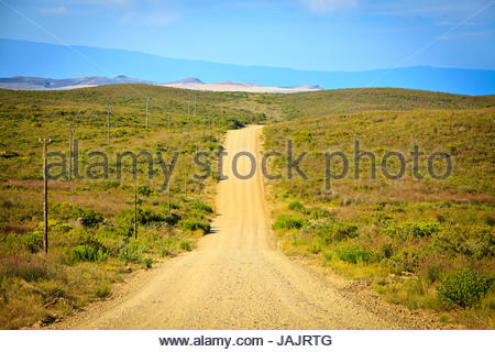 Gravel road stretching out towards the horizon Overberg South Africa - Stock Photo
