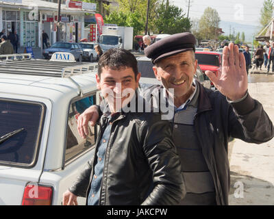 Two smiling Azerbaijani men and a taxi outside the daily market in Sheki or Shaki wanting to be photographed - Stock Photo