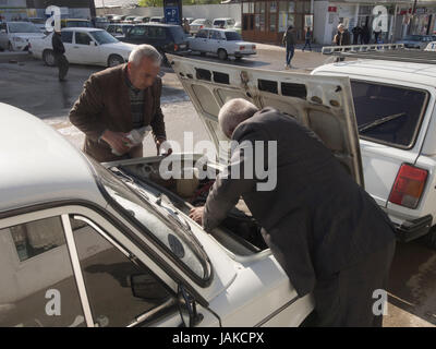 Two Azerbaijani men doing maintenance work to a taxi outside the daily market in Sheki  while eating for customers - Stock Photo