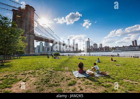 People enjoying free time on sunny day near Brooklyn Bridge in New York City - Stock Photo