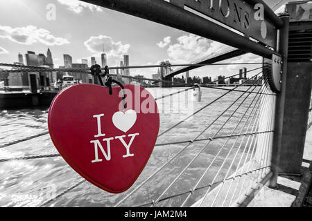 Black & white New York City photo with with red color hearth shape on the fence, Mahnattan and Brooklyn bridge on - Stock Photo