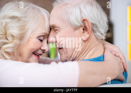 Happy senior couple embracing and touching foreheads at home - Stock Photo