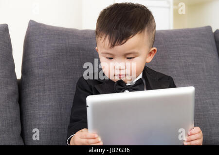 Asian little boy watching on tablet computer - Stock Photo