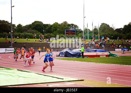 Children running a race at a track on an overcast day in Dublin Ireland kids athletics fitness health healthy living - Stock Photo