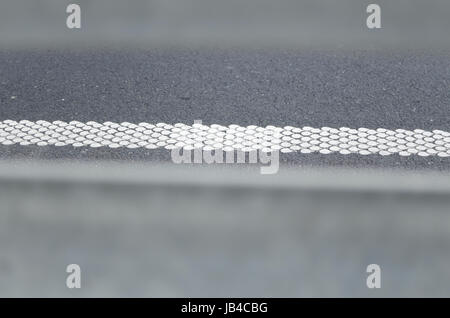 White Rumble Strip on the Road thru Crash Barriers - Stock Photo