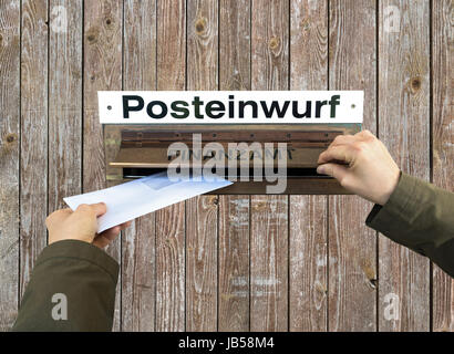 Hands post a letter into letterbox of finance office, Finanzamt. - Stock Photo