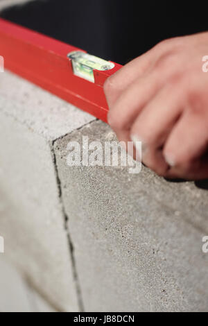 construction worker, bricklayer or mason laying bricks and creating walls. Detail of level tool - Stock Photo