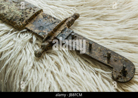 Antique real sword on a handmade wool blanket - Stock Photo
