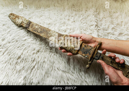 Laying the antique real sword on a handmade wool blanket - Stock Photo