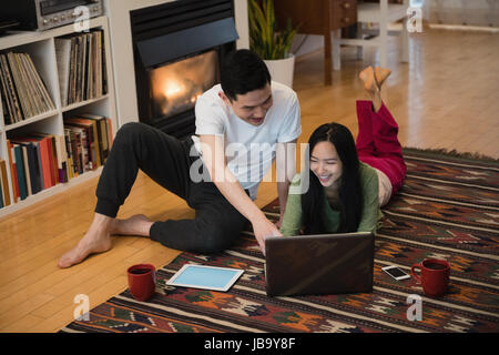 Happy couple using laptop near fireplace in living room at home - Stock Photo
