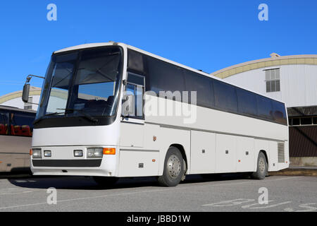 White coach bus on a bus parking area on a sunny day waiting for passengers. - Stock Photo