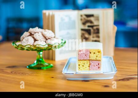 Yummy sponge cake and cookies for you. Enjoy them. Baking book in the background. - Stock Photo