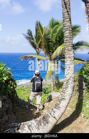 Tourist photographs rugged and jagged coastal feature of coral along Togo Chasm coast with Pacific Ocean beyond - Stock Photo