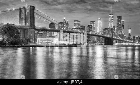 Black and white photo of Brooklyn Bridge and Manhattan at night, New York City, USA. - Stock Photo