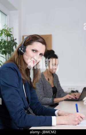 Eine junge Büroangestellte mit Headset schreibt in ein Dokument. Eine weitere Frau mit Headset befindet sich im - Stock Photo