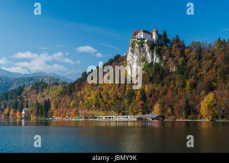 Bled Castle as seen across the lake in autumn - Stock Photo