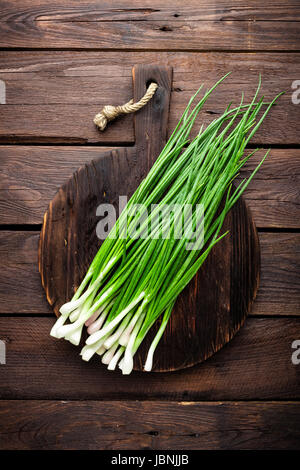 Green onion or scallion on wooden board, fresh spring chives - Stock Photo