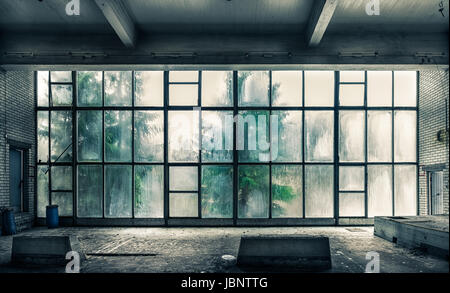 The view from an old, abandoned factory on the inside with nice window light - Stock Photo