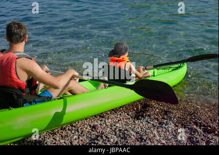 Two people - an adult and a child father and son in life jackets sail on inflatable boats during hike at summer - Stock Photo