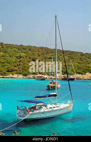 Cruising yacht at anchor in Poyraz bay, Karaada, near Bodrum Turkey. - Stock Photo