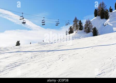 ski lift and slope of Dolomites mountains in Val Gardena, Italy - Stock Photo