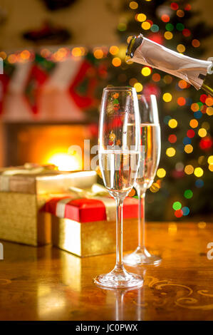 Closeup photo of two glasses being filled with champagne at Christmas eve - Stock Photo